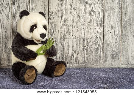 old vintage panda soft toy in the children's room on wooden background with copy space