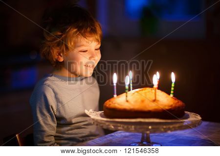 Little kid boy blowing candles on birthday cake