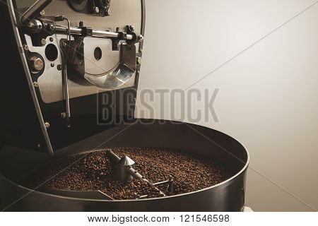 Freshly baked aromatic and dark coffee beans in the best professional roasting machine Industrial co