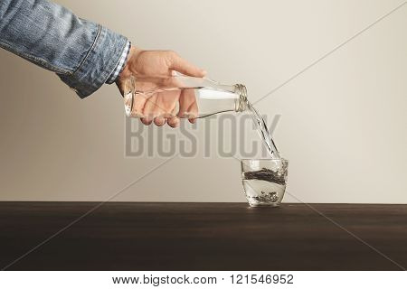 Man hand in blue denim jacket pours clean healthy water from transparent glass bottle to cup on wood