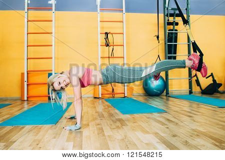 Fitness girl training trx push-up in gym