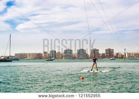 Cute Girl Learns To Surf On Background Of Yachts In Marina Of Torrevieja, Valencia, Spain