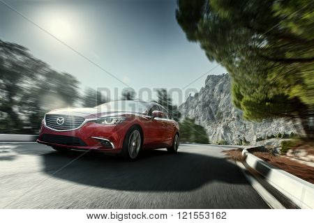 Red car Mazda speed driving on asphalt road near mountain at daytime