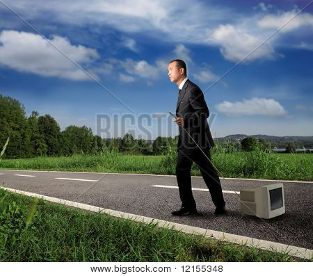 asian businessman dragging an old computer on the road