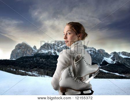 female ice skater portrait against a mountain landscape