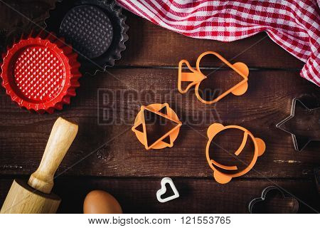 Baking/cooking props: cookie cutters, kitchen towel, rolling pin, pie shells and eggs on brown wooden background. Holiday baking cookies concept
