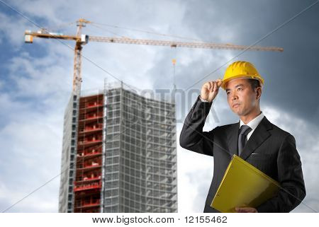 business man with hard hat in a erection yard