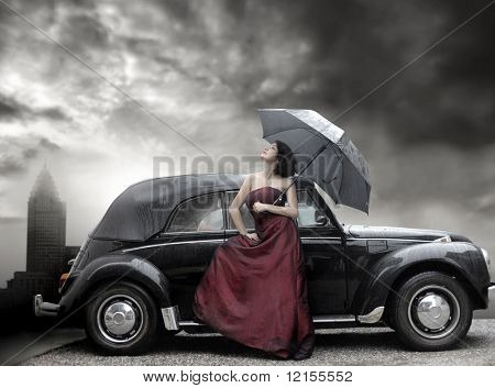 lady in purple dress and holding umbrella next to vintage luxury car