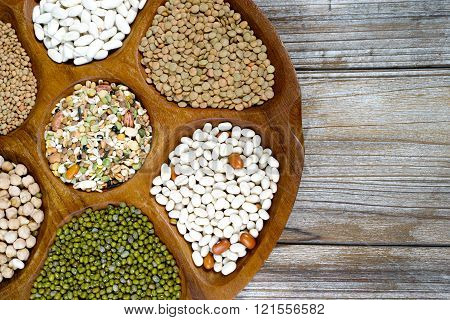 Wooden bowl of various legumes (chickpeas lentils green lentils green mungbeans) on wooden background