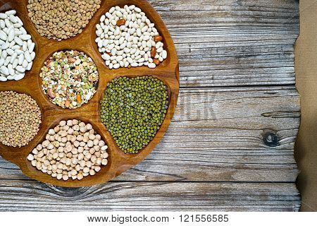 Wooden Bowl Of Various Legumes On Wooden Background Copy Space