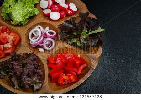 Wooden Bowl With Mixed Ingredients For Fresh Vegetable Salad