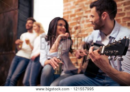 Young company playing guitar