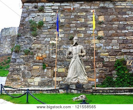 Ukrainian Cossack Statue of stone on a background of an old castle wall