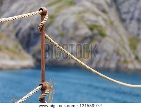 rope to an iron rod attached before sea and mountains