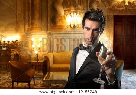 elegant guy holding a glass of wine in a luxury interior