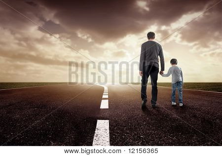 rear view of father and son walking on a street at sunset