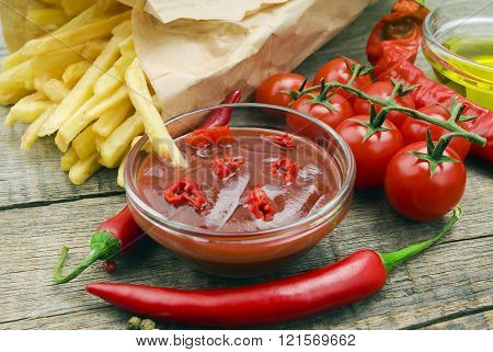 fried potatoes with peppers, tomatoes and ketchup on the wooden table