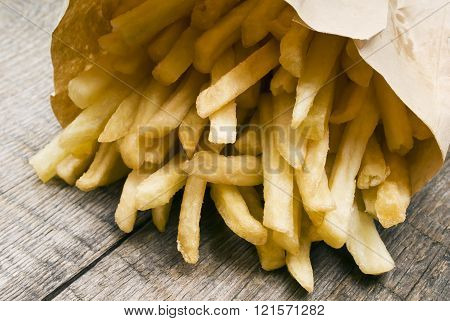 Potatoes fries in a little white paper bag