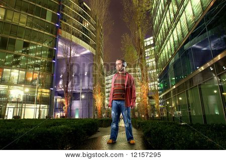 man listening music with headphones in a city street