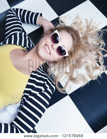 Young attractive blonde woman wearing sunglasses lying down on a checkered floor