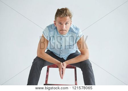 Brutal man in a shirt with short sleeves sitting on a red chair his fists clenched slightly bent und