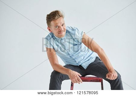 Brutal man in a shirt with short sleeves sitting on red chair his fists clenched slightly bent smili