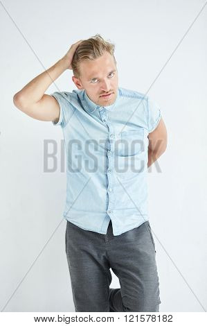 Brutal man with a small beard is leaning on the wall wearing a blue short-sleeved shirt and gray pan