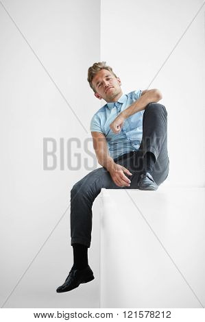 Brutal man with a small beard sitting on a wide windowsill a hand on his knee wearing a blue short-s