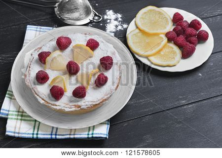 Lemon cake with raspberries slices of lemon sieve with icing sugar on a table of black color
