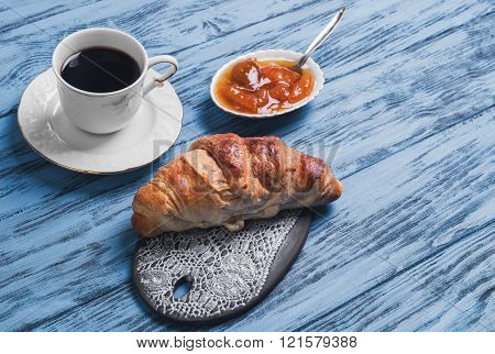 Croissant on a ceramic board apricot jam white cup of coffee on a wooden blue background empty space for your text