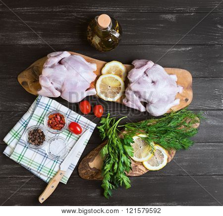 Two raw chicken carcasses cherry tomatoes dill parsley pepper salt crystal cutting board bottle of olive oil on a wooden background in rustic style top view