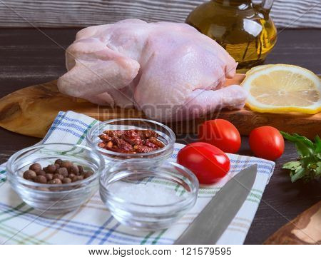 Raw chicken carcasses cherry tomatoes dill parsley pepper salt crystal cutting board bottle of olive oil on a wooden background in rustic style