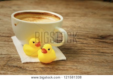 latte coffee with yellow rubber duck on background of wooden.