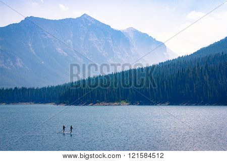 Mountain Lake Recreation. Paddle boarders drift through the Hyalite Reservoir in Montana. Nature landscape background with copy space.