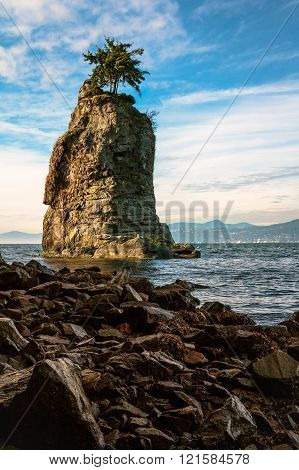 Siwash Rock Natural Landmark. Rocky Seashore of Stanley Park in Vancouver, British Columbia, Canada. Vertical Landscape.