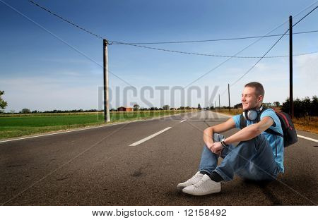 Portrait of a young man with headphones and a rucksack sitting on a countryside road
