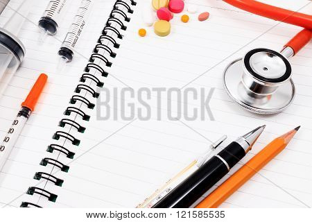 Red stethoscope, syringes, pen, pencil and many colorful pills on blank notepad