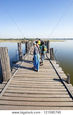 AMARAPURA, MYANMAR - NOVEMBER 27, 2015: Photo of a  group of Burmese people walking across U Bein Bridge (longest teak bridge in the world).