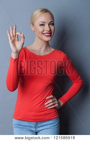 Beautiful blond girl is showing ok sign