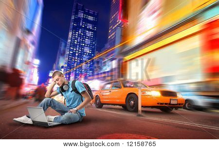 Portrait of a student sitting in the middle of a city street and using a laptop