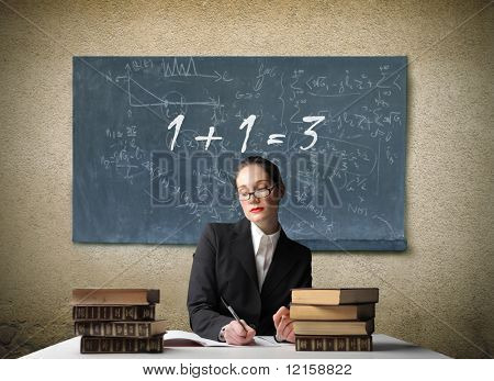 Portrait of a school teacher sitting at a desk with a blackboard with a wrong addition on it