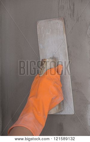 hand of builder worker use trowel plastering concrete at wall