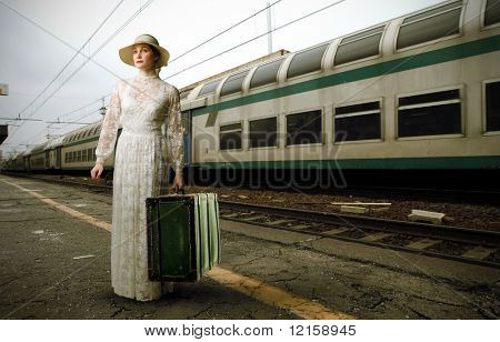 Portrait of an elegant woman standing on the platform of a train station with a suitcase in her hands