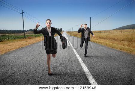 Retrato de um homem de negócios e uma empresária correndo em um rua de campo