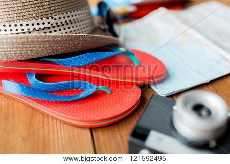 summer vacation, tourism and objects concept - close up of travel map, flip-flops, hat and camera
