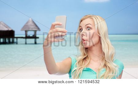 expressions, technology, travel, tourism and people concept - funny young woman or teenage girl taking selfie with smartphone and making fish face over tropical beach with bungalow background
