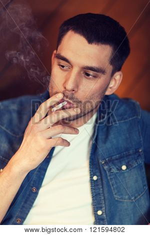 people and bad habits concept - young man smoking cigarette at bar