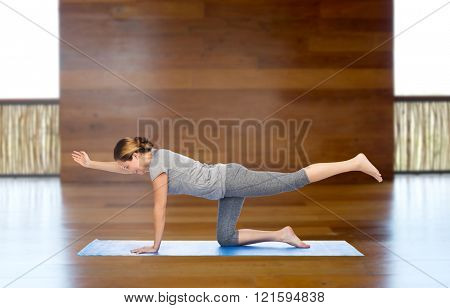 fitness, sport, people and healthy lifestyle concept - woman making yoga in balancing table pose on mat over wooden gym background
