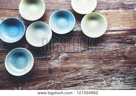 Handmade ceramic dishes on an old vintage table, top view