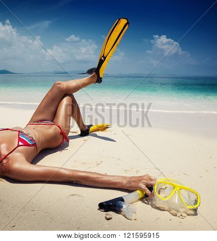 Young woman lying on the beach with fins and snorkeling gear